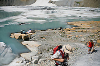 Hikers walk at the base of Grinnell Glacier in Glacier National Park in Montana.  The water is from the melting glacier.  Scientists predict that if current global warming trends continue, many of the the park's glaciers will disappear.