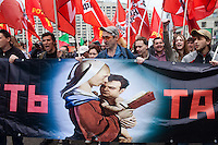 "Moscow, Russia, 01/05/2011..Anti-government demonstrators carrying a banner reading ""Throw down the tandem"" and depicting Putin as the Madonna holding his child Medvedev, as a mixture of Communist and anarchist anti-government groups demonstrate in central Moscow. A variety of political groups took to the streets on the traditional Russian Mayday holiday."