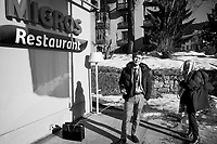 """Switzerland. Canton Graubunden. Davos. 50th edition of the World Economic Forum (WEF). A Japanese businessman charges his mobile phone by an outdoor electrical outlet on the terrace of Migros Restaurant. The woman assistant checks her mails on her phone while covering her head with a scarf. Snow on the ground. Sunny day. The World Economic Forum (WEF) Annual Meeting in Davos is the foremost creative force for engaging the world's top leaders in collaborative activities to shape the global, regional and industry agendas at the beginning of each year. It brings together 3,000 participants from around the world, and aim to give concrete meaning to """"stakeholder capitalism"""", assist governments and international institutions in tracking progress towards the Paris Agreement and the Sustainable Development Goals, and facilitate discussions on technology and trade governance. Migros is Switzerland's largest retail company, its largest supermarket chain and largest employer. It is also one of the forty largest retailers in the world. It is structured in the form of a cooperative society (the Federation of Migros Cooperatives). 22.01.2020 © 2020 Didier Ruef"""