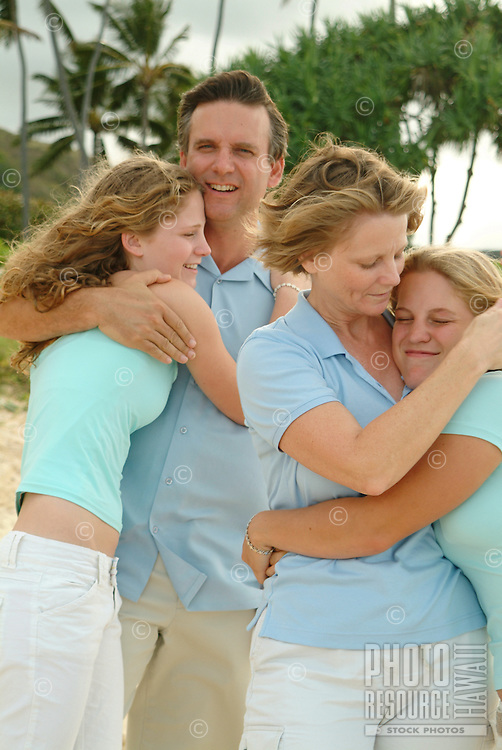 Father and mother with two daughters at the beach on a family vacation