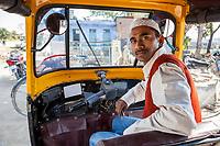 India, Dehradun.  Driver of Three-wheeled Taxi.