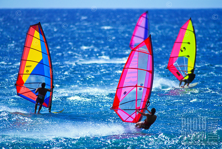 Windsurfers with their colorful sails cut through the blue ocean at Sunset beach, Oahu