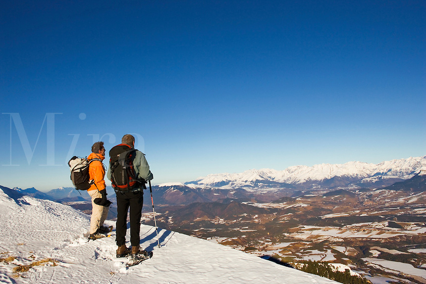 Two walkers on snow shoes stand on a ridge of Mont Barral,  Diois, Drome, Rhone-Alpes, looking towards Parc National des Ecrins, Isere, across the valleys of the Ebron and Drac.  France.  Model released.