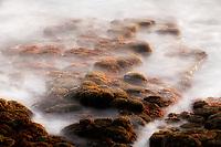 Ocean waves cover rocks. Poipu, Kauai, Hawaii