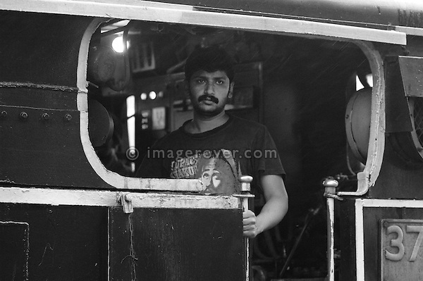 """Engine driver in the steam locomotive """"Nilgiri Queen"""" of the Nilgiri Mountain Railway at Coonoor Station. India, Tamil Nadu 2005. --- Info: The Nilgiri Mountain Railway (NMR) is the only rack railway in India and connects the town of Mettupalayam with the hill station of Udagamandalam (Ooty), in the Nilgiri Hills of southern India. The construction of the 46km long meter-gauge singletrack railway in Tamil Nadu State was first proposed in 1854, but due to the difficulty of the mountainous location, the work only started in 1891 and was completed in 1908. This railway, scaling an elevation of 326m to 2,203m and still in use today, represented the latest technology of the time. In July 2005, UNESCO added the NMR as an extension to the World Heritage Site of Darjeeling Himalayan Railway."""
