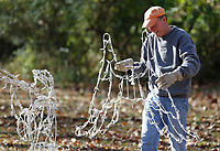 Monty Henderson carries a set of wings Monday, November 16, 2020, for an angel decoration in his yard off of Old Missouri Road in Fayetteville. Henderson has been using the same decorations for 25 years and said he only has to change the occasional light bulb. Check out nwaonline.com/201117Daily/ and nwadg.com/photos for a photo gallery.(NWA Democrat-Gazette/David Gottschalk)