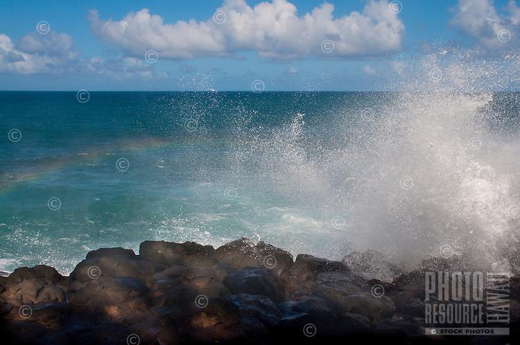 A wave reflecting a rainbow at the Queen's Bath area of Princeville, Kauai.