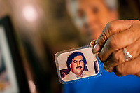 "Rosalvina Vargas de Gallego, one of the first inhabitants of the Pablo Escobar neighborhood, shows a picture of Pablo Escobar kept in her wallet, in Medellín, Colombia, 30 November 2017. Twenty five years after Pablo Escobar's death, the legacy of the Medellín Cartel leader is alive and flourishing. Although many Colombians who lived through the decades of drug wars, assassinations, kidnappings, reject Pablo Escobar's cult and his celebrity status, there is a significant number of Colombians who admire him, worshipping the questionable ""Robin Hood"" image he had. Moreover, in the recent years, the popular ""Narcos"" TV series has inspired thousands of tourists to visit Medellín, creating a booming business for many but causing a controversial rise of narco-tourism."