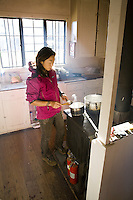 Woman cooking breakfast in a cabin in Haleakala National Park
