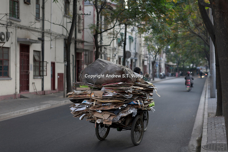 A man collects recyclable rubbish in Shanghai, China on November 05, 2009.