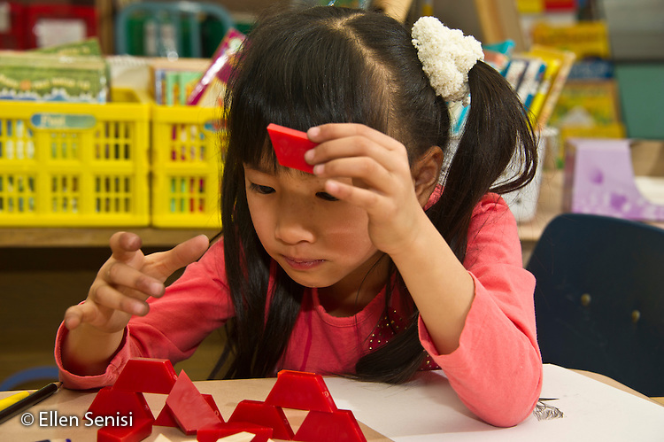 MR / Schenectady, New York. Paige Elementary School (urban public elementary school). First grade independent work at learning center time. Student (girl, 6, Chinese American) watches shape pattern blocks structure she has made collapse at math learning center. MR: Wil40. ID: AL-g1g. © Ellen B. Senisi.