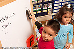 Preschool Headstart 3-5 year olds boy using eraser to clean board in classroom horizontal