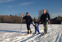 A family cross country skiing; mother, father, toddler.