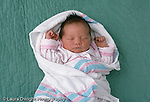 newborn baby girl 3 days old lying on back swaddled in hospital blanket asleep Caucsian horizontal