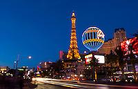 Las Vegas Nevada gambling on The Strip with Paris Casino at night exposure and traffic moving energy of Las Vegas Blvd