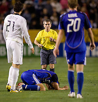 Referee Michael Kennedy pulls out a yellow card out of his pocket ready to make a call as LA Galaxy forward Alan Gordon (21) and Wizards defender Tyson Wahl (20) look on while hovering over Wizard midfielder Jack Jewsbury (14) on the ground during the second half of a MLS match. The LA Galaxy defeated the Kansas City Wizards 3-1 at Home Depot Center stadium in Carson, Calif., on Saturday, May 24, 2008.