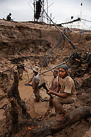 "Workers crowded together and fixing muddy sluice box are: Rohani, Suyanto, Nano, Imam, Eko, Purwanto--all from east Java and none of them have last names.  The two miners panning with mercury in the amalgam pond are: Ibrahim and Oon.  East Java has high unemployment and there are many migrant workers on Kalimantan (Borneo) from Java who came initially to do artisanal timber work.  The government stomped out the little guys in timber in favor of two big companies so they could control (read ""profit from"") the industry.  So all the artisanal timber workers switched to gold. Karang Pani is a new regency established by the government--The town is only 3 years old and is support center for the artisanals--providing diesel engines, retorts to purify amalgam and other services.  The gold mining area is called Galangan and is about 11KM out of town. There are 15 retorts in Karang Pani and the mercury goes up in the smoke but then rains down on the town.  Miners test in the 1000 plus area for ppm of mercury--normal is 170 to 300 depending on how many mercury fillings you have (results of Unido testing in area).  Miners earn about $5USD a day.  E. Java is way overcrowded and the govt. has an official transmigration program over to Kalimantan.  In E. Java they can earn about 100RP a day hoeing the fields, here they can earn upwards of 30,000-60,000RP ($3-$6) a day. So it is worth it to them to camp in this area having only the water from the amalgam ponds to bath and drink.  I have many photos of people brushing their teeth or bathing next to a guy panning with a big glob of mercury."