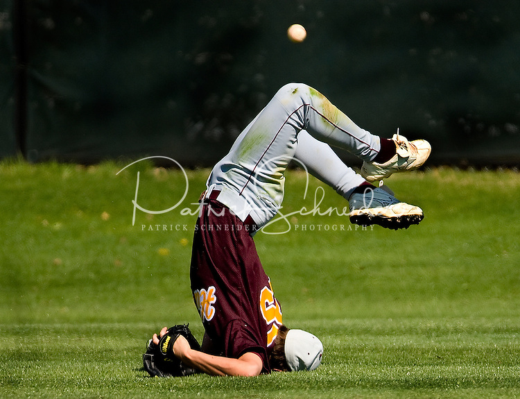 A baseball player hits the ground face first trying to make a catch.