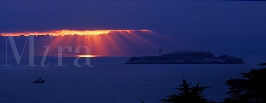 Sun rising over Alcatraz with sun breaking through the clouds