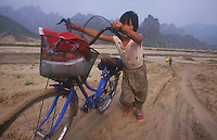 A girl pushes her bike through the sand in Fang Ning, LangTou Gou,China. Droughts and increasing desertification are causing ever-greater environmental problems in northern China...PHOTO BY WONG / SINOPIX
