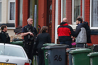 Pictured: David Campbell (also known as David Charmers in grey coat with black sleeves) is being led away by officers from a house in Raffles Road in Birkenhead, Merseyside, where armed police have placed a containment on a terraced house.<br />