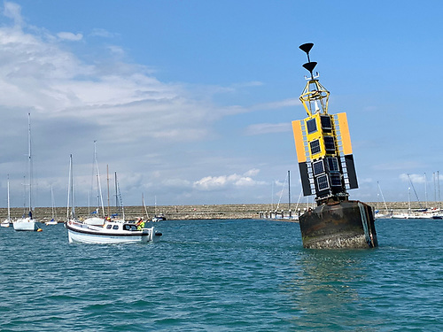 Small boat, big buoy. An Irish Lights tender tows a buoy back to the harbour depot at Dun Laoghaire