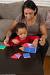 3 year old boy playing with magnetic building tiles, helped by his mother