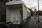 April 18, 2020<br /> Brooklyn, New York<br /> Fort Greene<br /> <br /> Mount Sinai Beth Israel with its white cooler trailer set outside to use as a morgue for those who died from the crononavirus. Pedestrians pass by as it has become a part of everyday life in the New York.