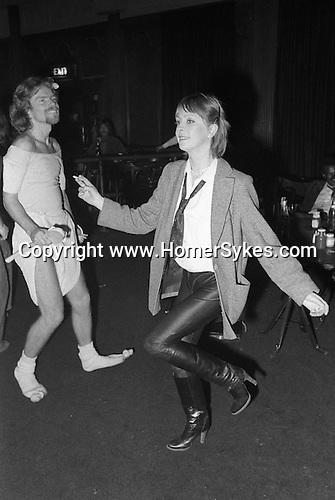 Virgin record boss Richard Branson dressed in nappies baby grow and holding a wooden bath brush dances the night away at The Venue. It's his fancy dress party. Central London, England. November 1978.
