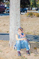 A woman sits against a tree holding American flags as alt-right organization Super Happy Fun America demonstrates against facemasks, vaccines, and pandemic closures, and in support of the reelection of President Donald J. Trump near the residence of Massachusetts governor Charlie Baker in Swampscott, Massachusetts, on Sat., Sept. 26, 2020. Super Happy Fun America is most well known for organizing the Straight Pride Parade in Boston on August 31, 2019.