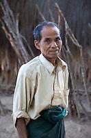 Myanmar, Burma.  Middle-aged Burmese Man in Village near Bagan.  His longyi is tied in a knot in front.  Burman (Bamar) Ethnic Group.