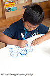 Education Preschool 3-5 year olds art activity boy drawing recognizable figures with marker using right hand and correct grip vertical