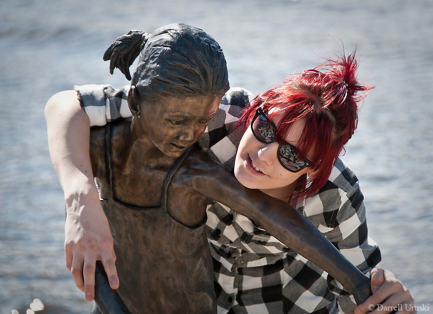 Street photography of a lady posing with a statue at the beach.