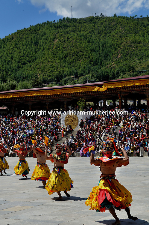 """Monks perfom during annual Thimpu Tshechu. The Tshechu is a festival honouring Guru Padmasambhava, """"one who was born from a lotus flower."""" This Indian saint contributed enormously to the diffusion of Tantric Buddhism in the Himalayan regions of Tibet, Nepal, Bhutan etc. around 800 AD. He is the founder of the Nyingmapa, the """"old school"""" of Lamaism which still has numerous followers. The biography of Guru is highlighted by 12 episodes of the model of the Buddha Shakyamuni's life. Each episode is commemorated around the year on the 10th day of the month by """"the Tschechu"""". The dates and the duration of the festivals vary from one district to another but they always take place on or around the 10th day of the month according to the Bhutanese calendar. During Tshechus, the dances are performed by monks as well as by laymen. The Tshechu is a religious festival and by attending it, it is believed one gains merits. It is also a yearly social gathering where the people, dressed in all their finery, come together to rejoice. Arindam Mukherjee."""