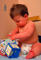 Baby in diaper playing with toys.
