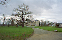 The chateau de Fesles, Anjou, Thouarcé (Maine-et-Loire) near BONNEZEAUX in winter. A view over the main building, the green grass lawn and a big black tree in silhouette without leaves leaf. An arrow pointing visitors to the right, Maine et Loire France