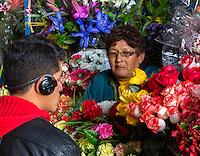 Peru, Cusco.  San Pedro Market.  Flower Vendor and Customer.