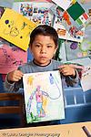 Education Preschool 4-5 year olds art activity proud boy showing his drawing recognizable human figure or superhero vertical