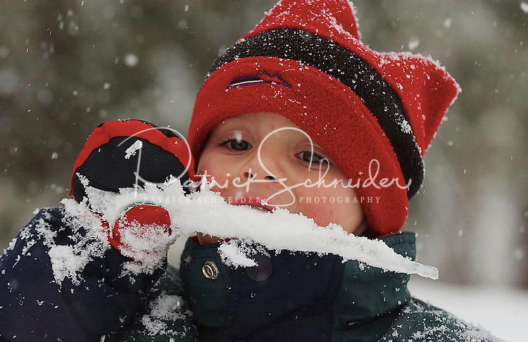 A young boy bites an icicle while playing the snow.