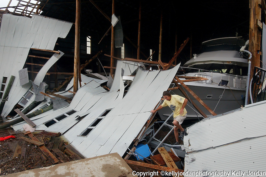 """Kevin Dyke, of Daytona Beach, carefully makes his way through the debris at the Daytona Marina and Boat Works to get from his fishing boat """"Paradise"""" to his car parked at the marina. Dyke, who says he stayed at his boat through the storm and also helped to secure other boats throughout the night says his boat is not damaged.(Kelly Jordan)"""