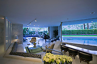 Contemporary living room with a grand piano and pool in background