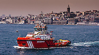 Fine Art Landscape Photograph. <br /> Tugboat on the Bosphorus Strait in Istanbul, Turkey.<br /> A colourful red tugboat casts it's reflection on the water as it sails on the Bosphorus Strait. <br /> The background scene of Istanbul's skyline with it's ancient buildings and architecture.