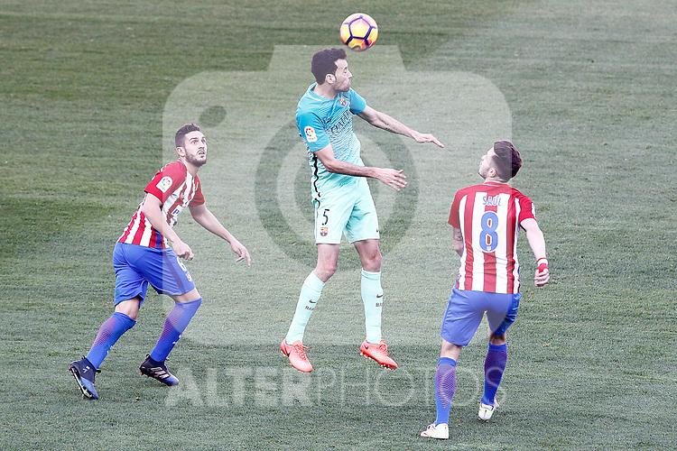 Atletico de Madrid's Koke Resurrecccion (l) and Saul Niguez (r) and FC Barcelona's Sergio Busquets during La Liga match. February 26,2017. (ALTERPHOTOS/Acero)