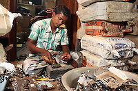 A man sorts through used electronics in a small village near Kolkata.<br />
