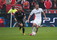 Toronto, Ontario - May 3, 2014: New England Revolution midfielder Andy Dorman #12 and Toronto FC defender Justin Morrow #2 in action during a game between the New England Revolution and Toronto FC at BMO Field.<br /> The New England Revolution won 2-1.
