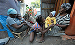 A family sits between tents in the largest temporary settlement of Haitian earthquake survivors, located on a former nine-hole golf course in Port-au-Prince. The Petionville Club is host to more than 44,000 people..
