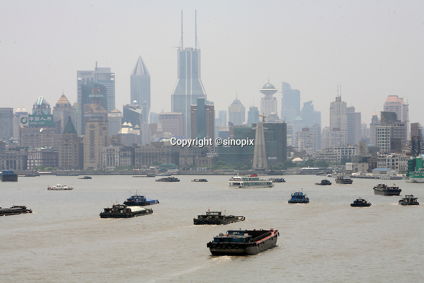 Barges travel on the Huangpu River past the Pudong Financial District in Shanghai, China..=