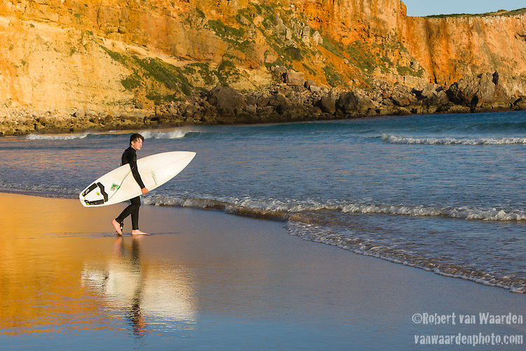 A young surfer walks into the waves while in the background the yellow red cliffs of Sagres reflect in the water of the Algarve region of Portugal.