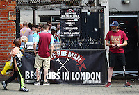 A local rib meat roll seller speaks with a customer while a West Ham fan with artificial leg looks on   before  the Barclays Premier League match between West Ham United and Swansea City  played at Boleyn Ground , London on 7th May 2016