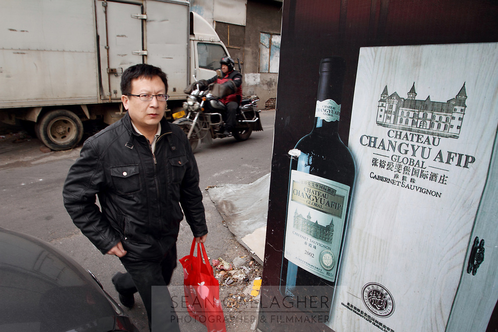 China. Jilin Province. A man walking past a advertisement for wine in the town of Yanji, close to the border with North Korea. The town is part of the Korean Autonomous Prefecture in the north-east of the country. 2011